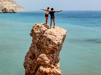 A couple at the top of a rock overlooking the ocean